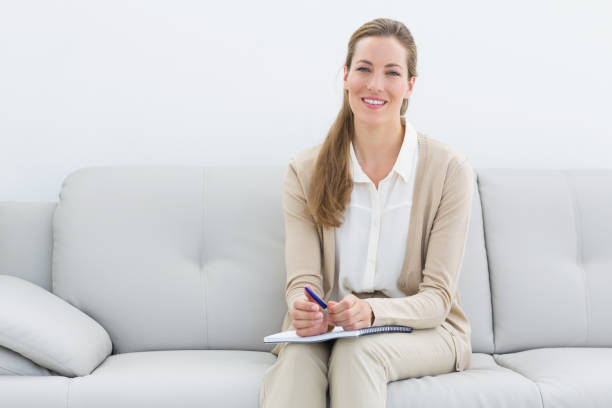smiling female psychologist sitting on sofa - psychiatrist stock photos and pictures