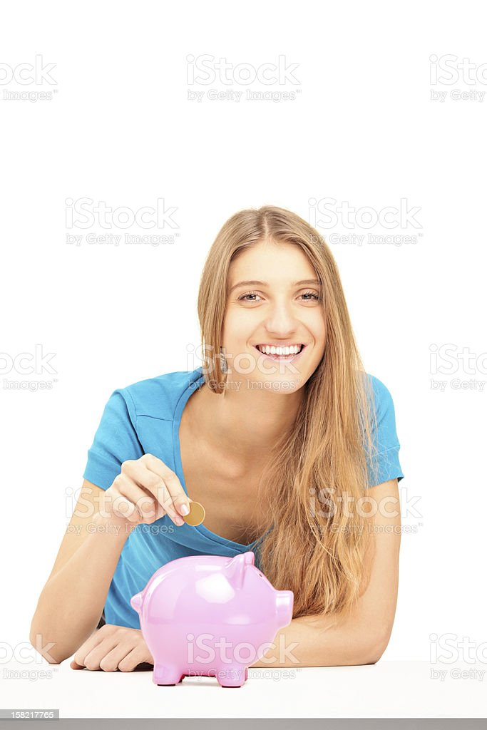 Smiling female putting a coin into piggy bank royalty-free stock photo