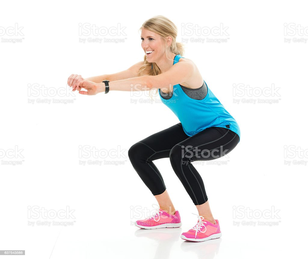 Smiling female runner squatting stock photo