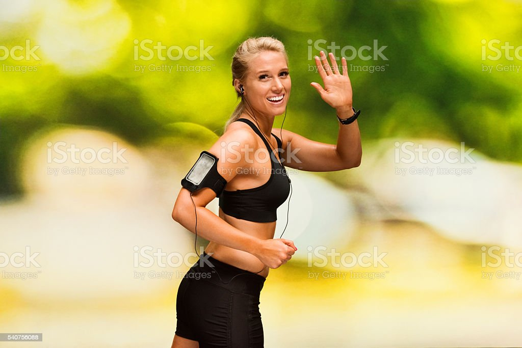 Smiling female runner waving hand stock photo