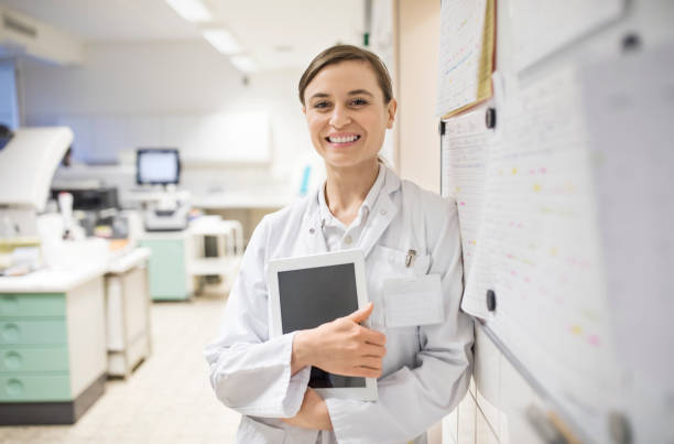 Smiling female scientist holding digital tablet stock photo