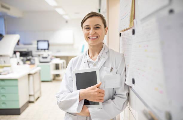 Scientifique de femme souriant tenant la tablette numérique - Photo