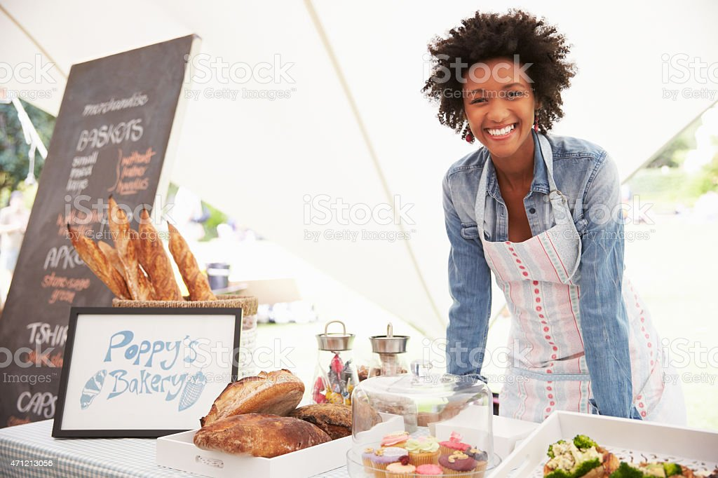 Smiling female selling food at a farmers food market stock photo