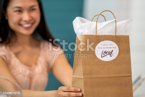 Asian boutique owner holding up a shopping bag with a