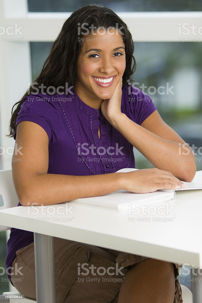 Smiling female sitting behind a desk with book royalty-free stock photo