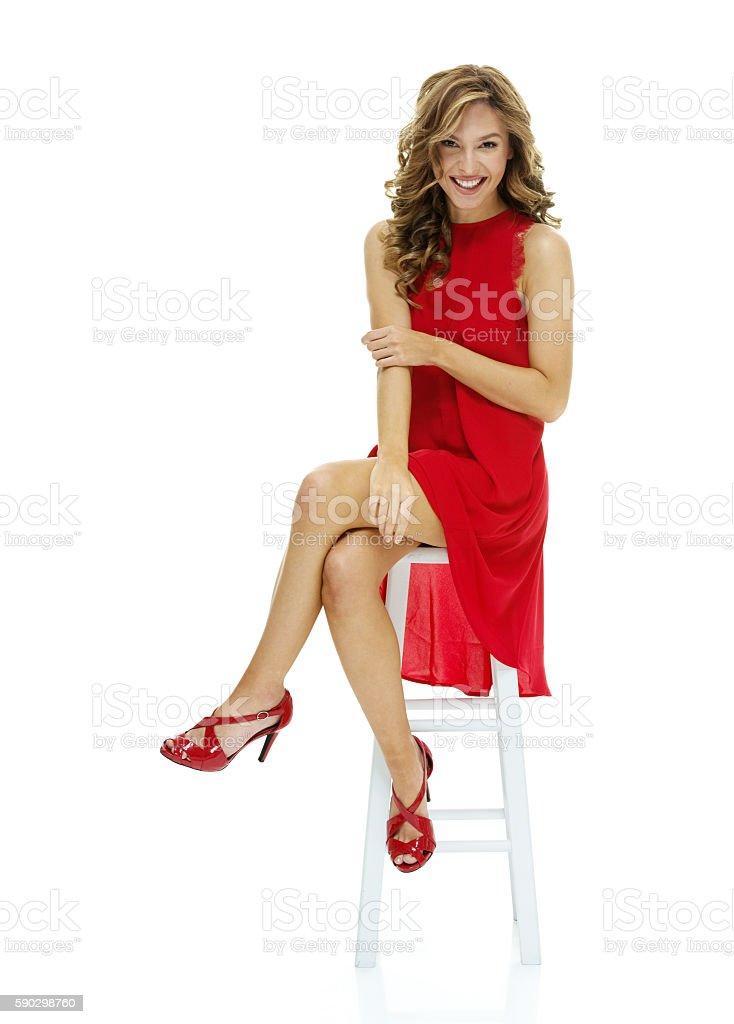 Smiling female sitting on stool royaltyfri bildbanksbilder