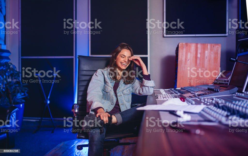 Smiling female sound technician in recording studio stock photo