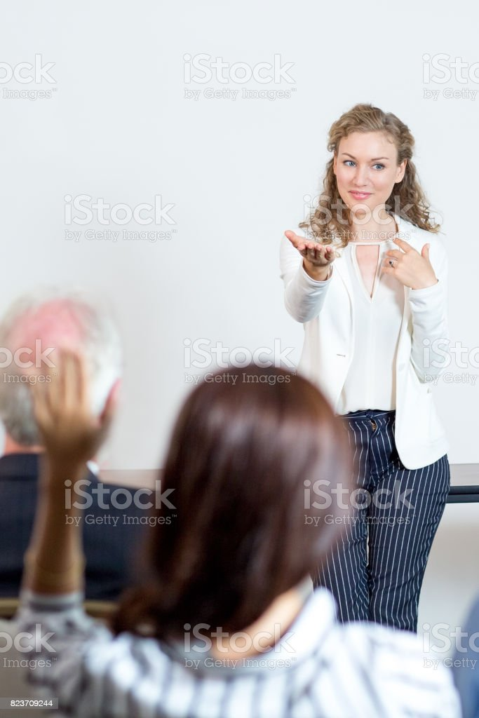 Smiling Female Speaker Giving Floor to Audience stock photo