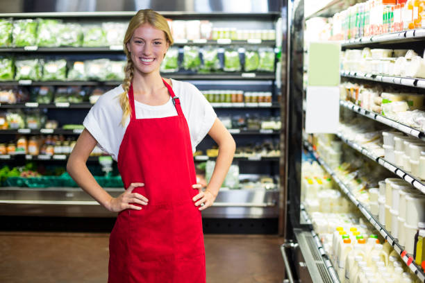 glimlachend vrouwelijk personeel staan met hand op heup in supermarkt sectie - verkoopster stockfoto's en -beelden