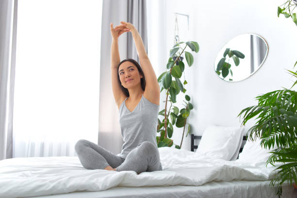 Smiling female starting morning with meditation at home stock photo