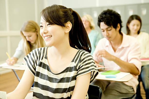 Sonriente mujer estudiante estudiando en clase - foto de stock