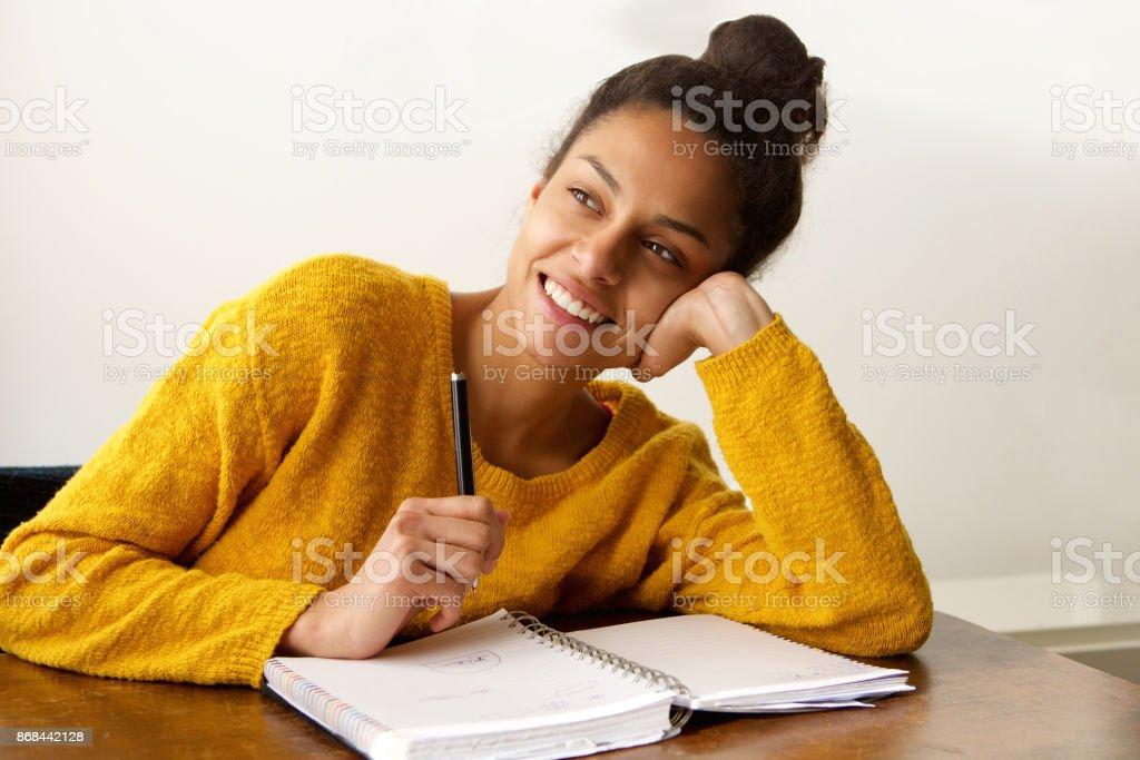 Souriante étudiante en pensée avec stylo et papier - Photo