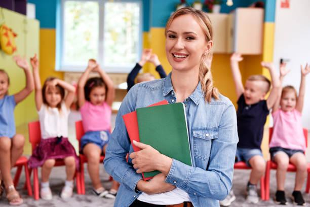 Smiling female teacher in the preschool stock photo