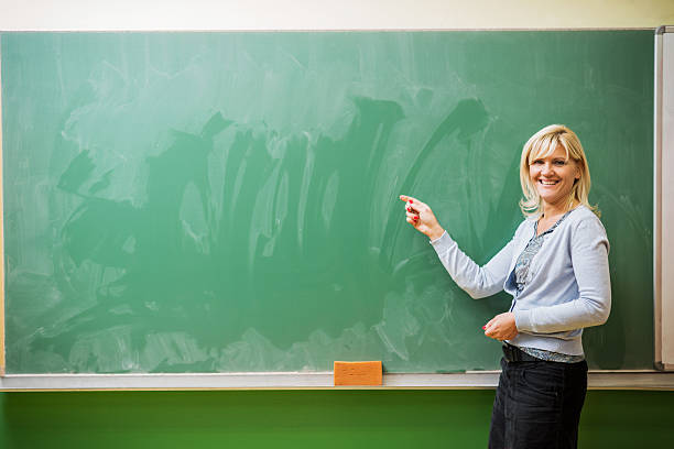 Smiling female teacher pointing at blackboard. Copy space. stock photo