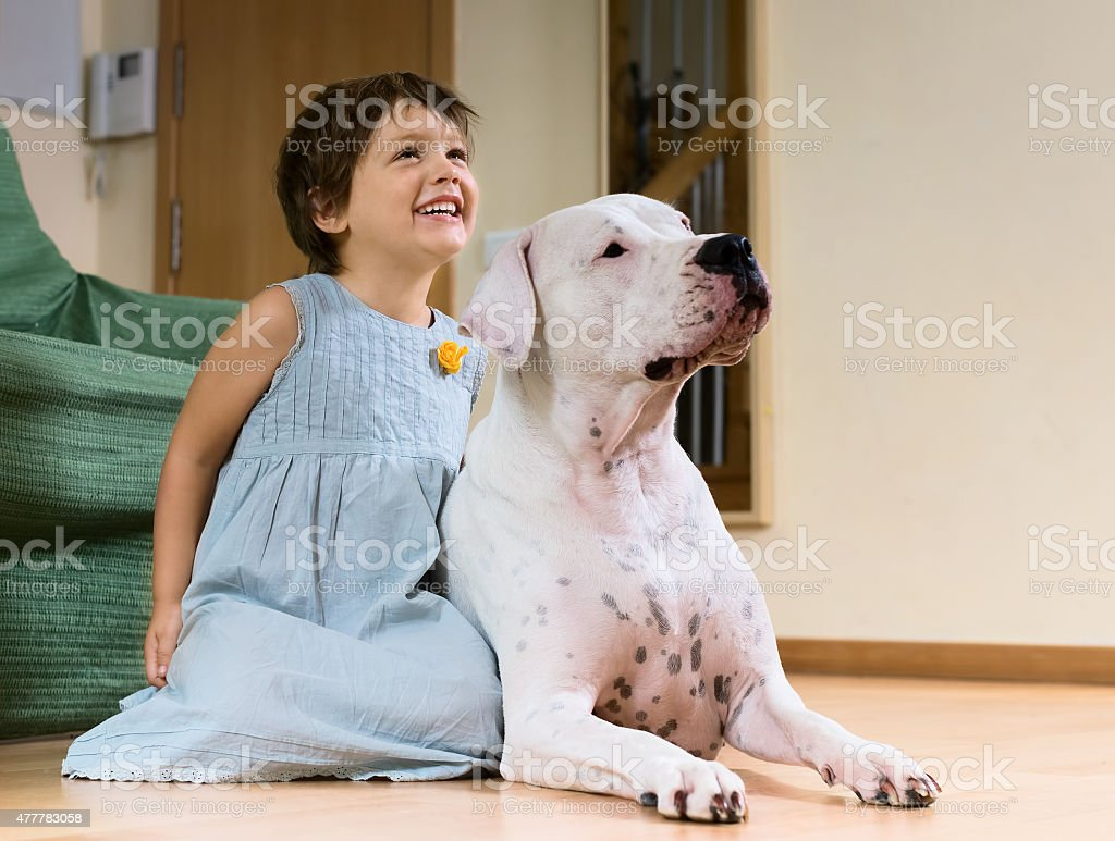 smiling female toddler on the floor with dog stock photo
