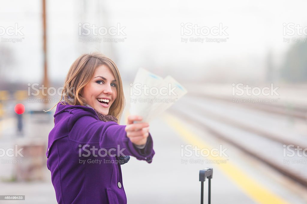 Smiling female traveler at railroad station with tickets stock photo