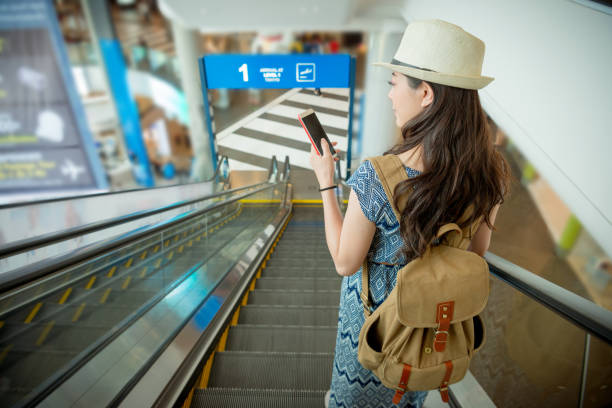 smiling female traveler using mobile smartphone stock photo