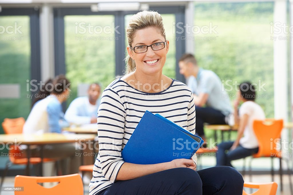 Smiling female tutor sitting in classroom - Royalty-free 30-39 Years Stock Photo