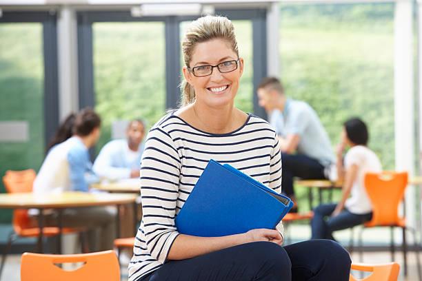 Smiling female tutor sitting in classroom stock photo