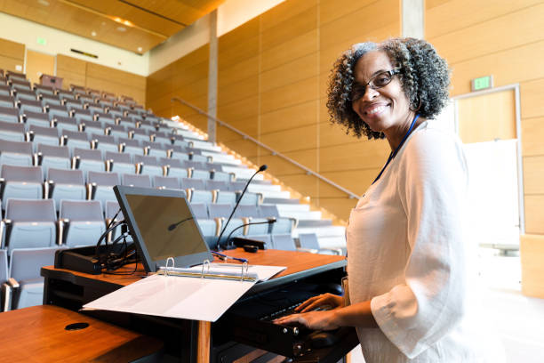 Smiling female university professor pauses work to pose for photo The cheerful, mature adult female university professor pauses in her class preparation to smile for the camera.  She is using the audio visual equipment. professor stock pictures, royalty-free photos & images