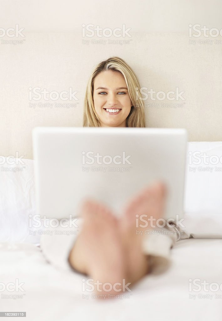 Smiling female using laptop while sitting in bed royalty-free stock photo