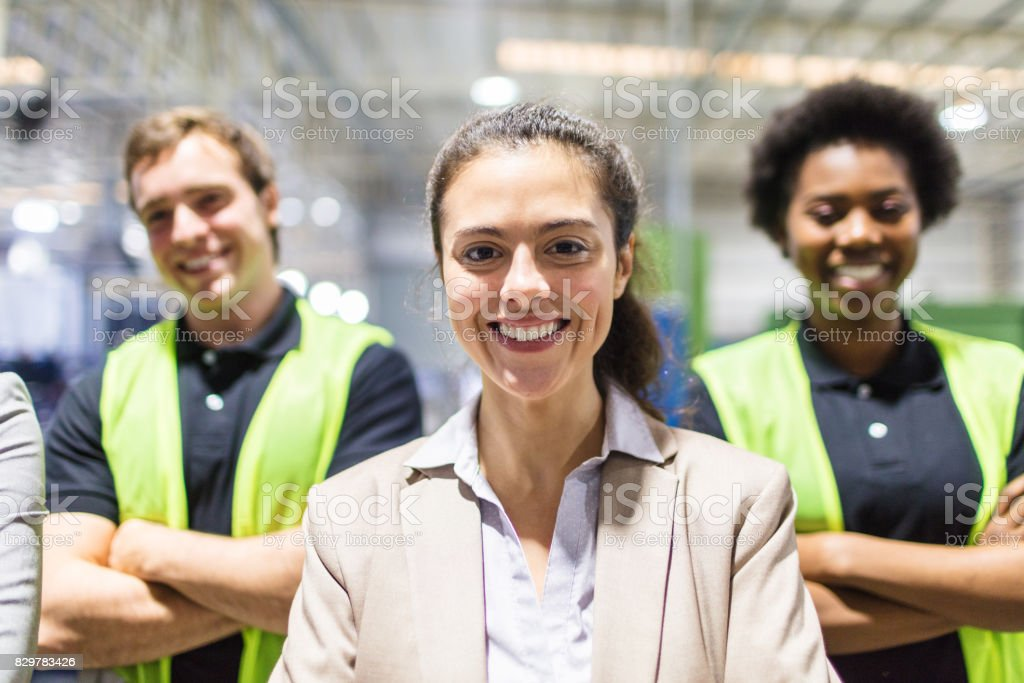 Smiling female warehouse manager with team in background stock photo