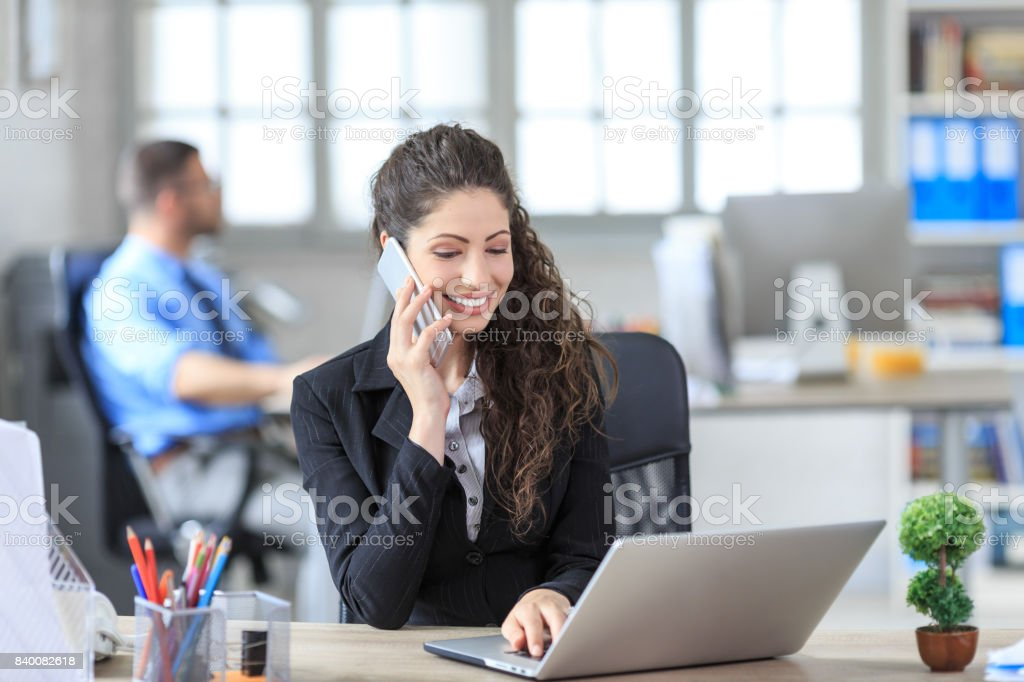 Smiling female white collar worker with suit talking on smart phone...