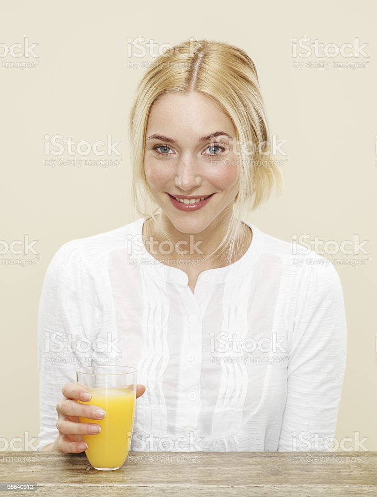 smiling female with glass of fresh orange juice royalty free stockfoto