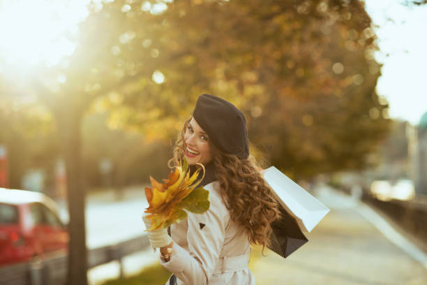 smiling female with shopping bags and autumn leaves stock photo