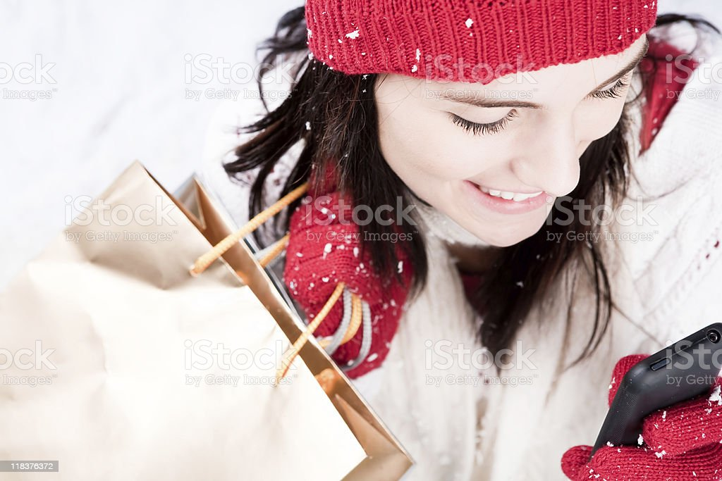 Smiling female with shopping bags texting on her phone royalty-free stock photo