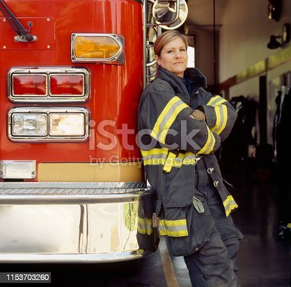 Smiling female woman firefighter with fire engine truck at station. Confident, successful public service career professional.