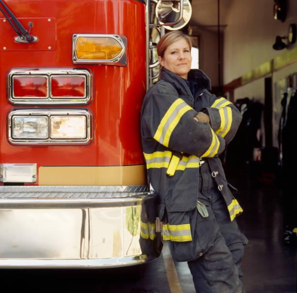 lächelnde feuerwehrfrau mit feuerwehrwagen am bahnhof zuversichtlich, erfolgreicher berufsprofessionell im öffentlichen dienst. - laschet stock-fotos und bilder