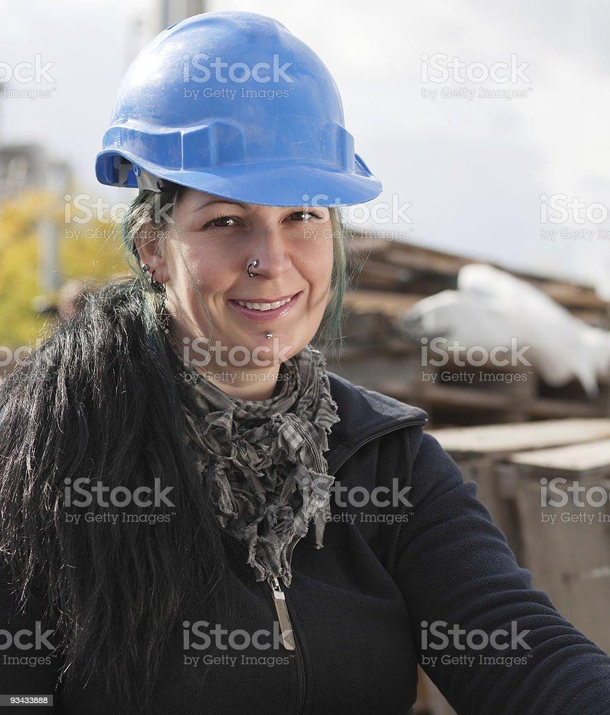 Lächelnd weiblichen Arbeiter in Blau Schutzhelm Lizenzfreies stock-foto