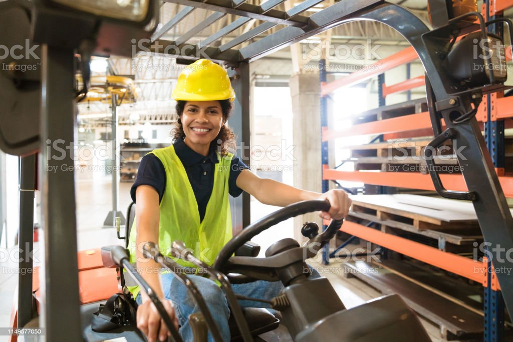 Smiling female worker sitting on forklift Portrait of smiling female worker sitting on forklift. Confident mid adult engineer is working in manufacturing factory. She is wearing hardhat and reflective clothing. 30-34 Years Stock Photo