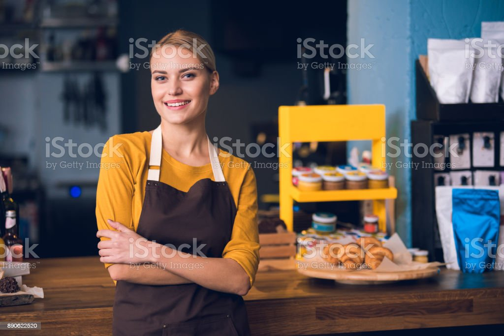 Smiling female worker situating in cafe stock photo