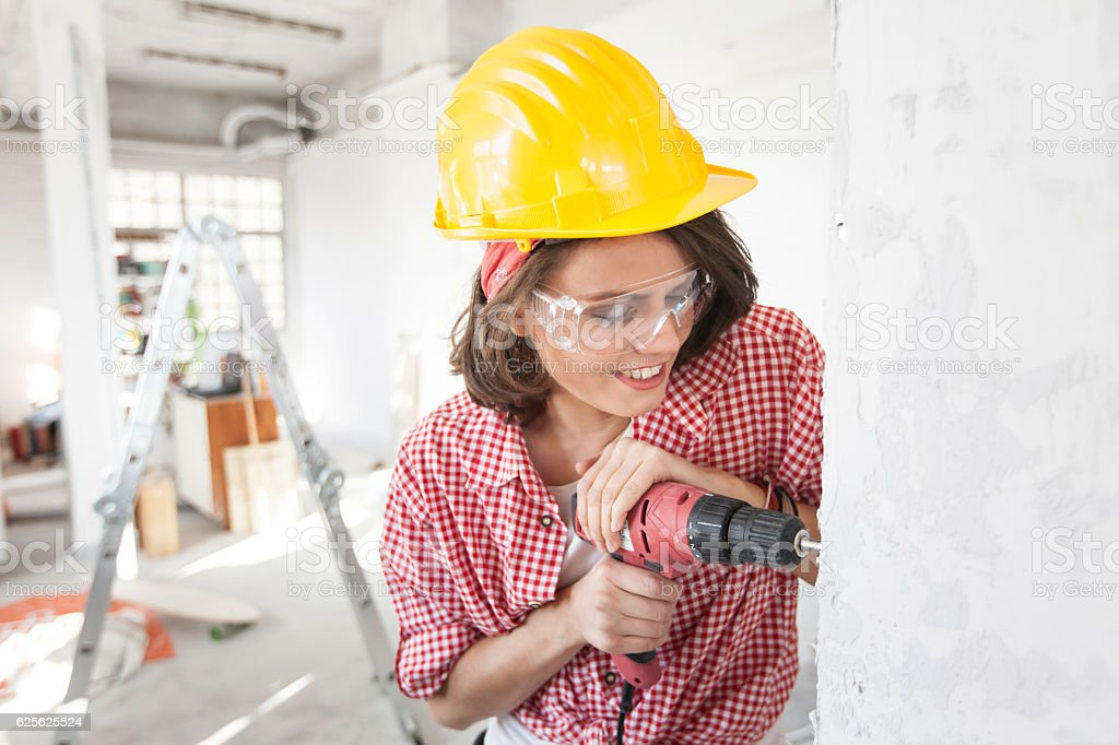 Smiling female worker using a drill stock photo