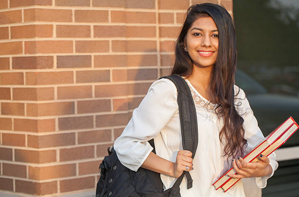 smiling female young college student of indian ethnicity - pakistano foto e immagini stock