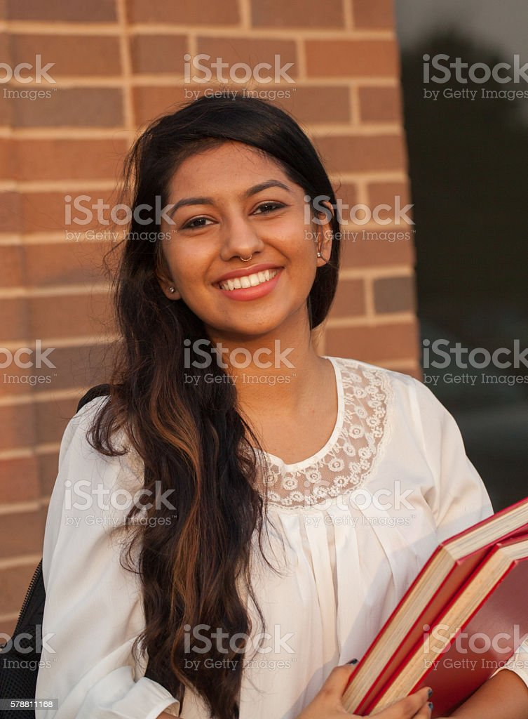 Smiling female young college student of Indian ethnicity carrying...