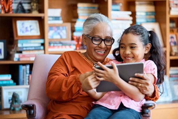 lächelnde frauen mit digital-tablette zu hause - enkelin stock-fotos und bilder