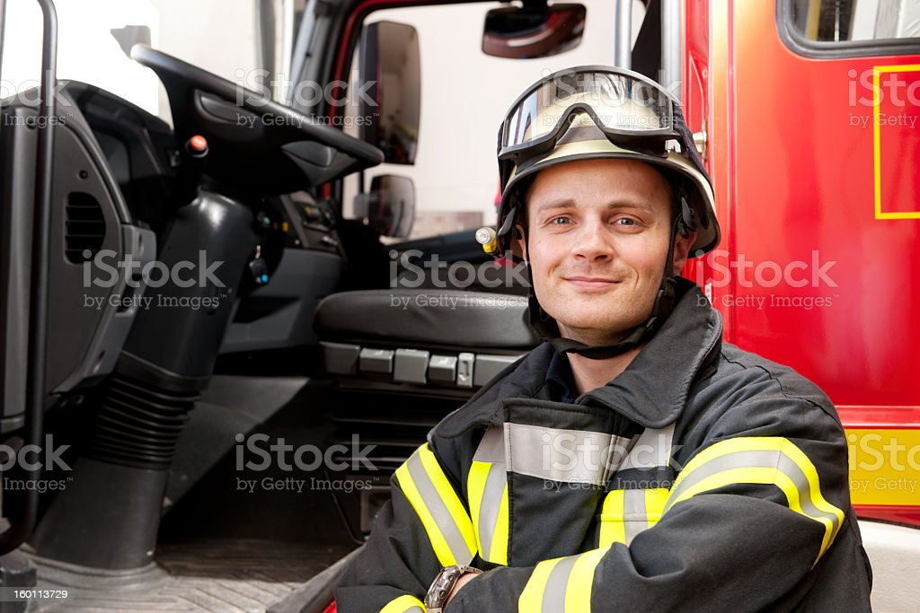 A smiling firefighter in his gear in front of his truck stock photo