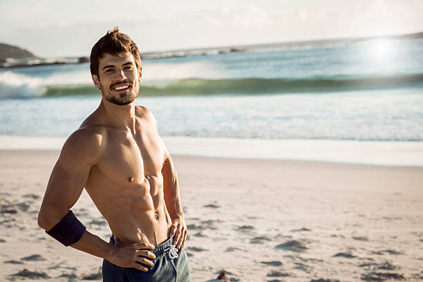 smiling fit man relaxing after workout strong fit man smiling and taking a break after hard workout,beautiful weather,sunny day,in the background waves splashing on the beach abdominal muscle stock pictures, royalty-free photos & images