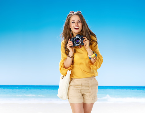smiling fit woman on seacoast with digital SLR camera