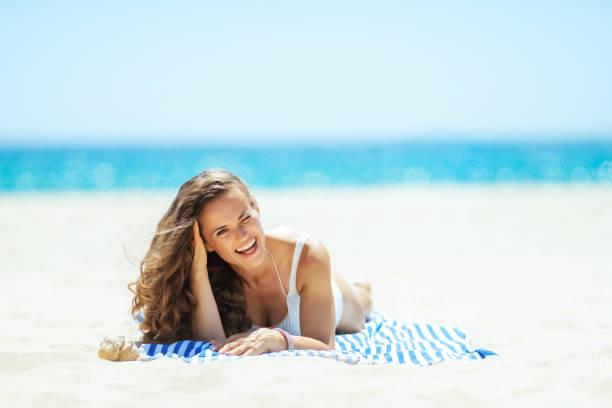 lächelnde Frau am Strand liegend auf gestreiften Handtuch passen – Foto