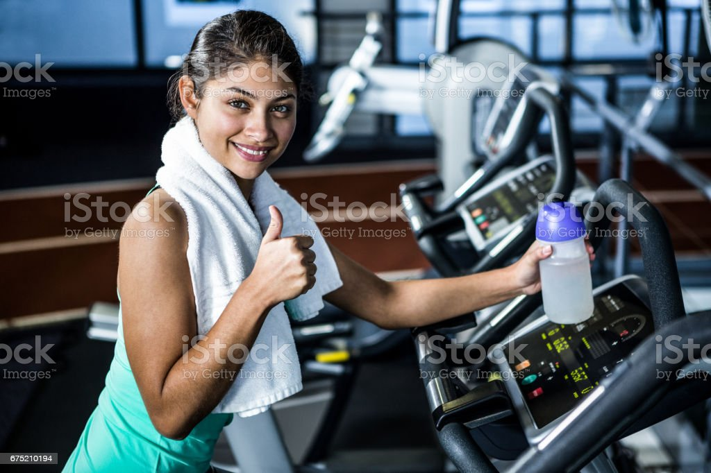 Smiling fit woman with thumbs up royalty-free stock photo