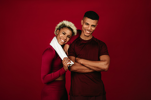 Cheerful african american couple in fitness wear standing together on maroon background. Fitness couple relaxing after workout.