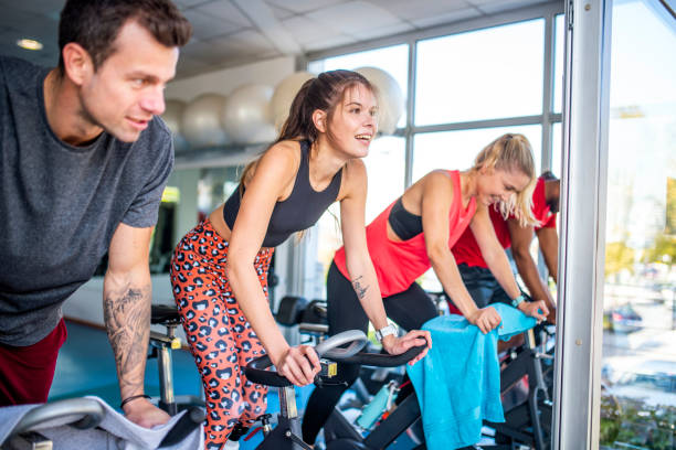 Smiling Fitness Enthusiasts Standing While Cycling at Gym stock photo