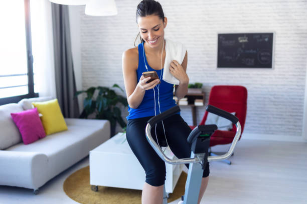 Smiling fitness girl using mobile phone after training on exercise bike at home. Shot of smiling fitness girl using mobile phone after training on exercise bike at home. exercise machine stock pictures, royalty-free photos & images