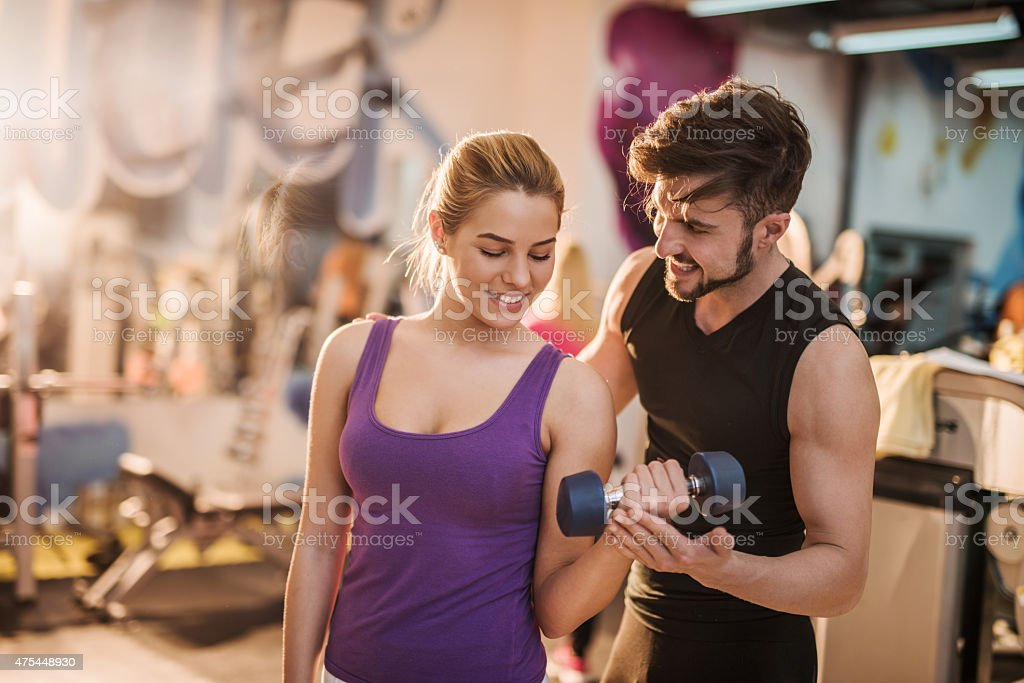 Smiling fitness instructor assisting young woman with weight exercises. stock photo