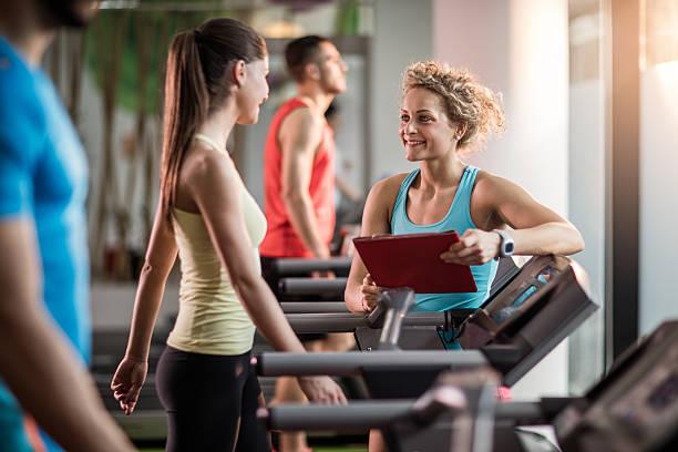 Souriant formateur parlant bonne forme de jeune femme dans une salle de sport. - Photo