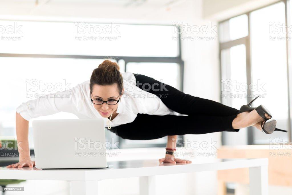 Smiling flexible woman watching at laptop stock photo